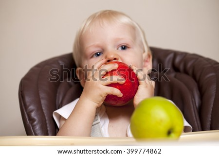 sharpness on the apple. Portrait of blonde baby boy sitting at the dinner table - stock photo