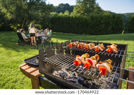 Shashlick laying on the grill with a group of friends in the background eating and drinking in the late sunny afternoon - stock photo