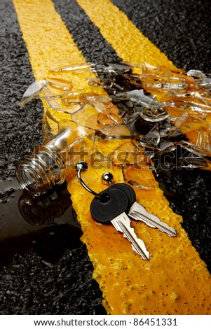 Shattered bottle of whisky on road with car keys - stock photo