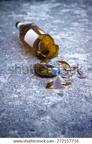 Shattered brown beer bottle resting on the ground: alcoholism concept - stock photo