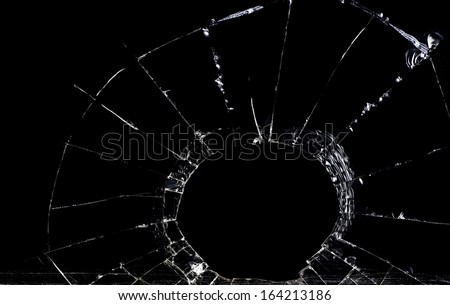 Shattered glass against a black backdrop is shown. - stock photo