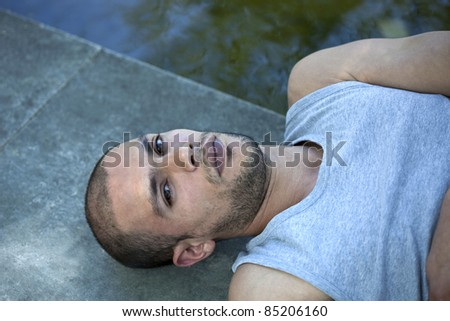 Shaved and bearded young man lying on the ground