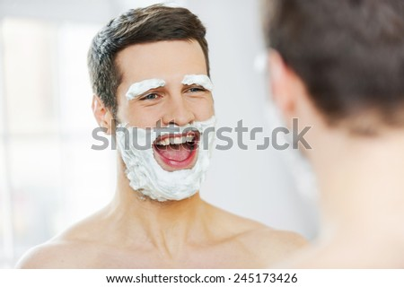 Shaving with fun. Rear view of playful young man with shaving cream on his face smiling while standing in front of the mirror - stock photo