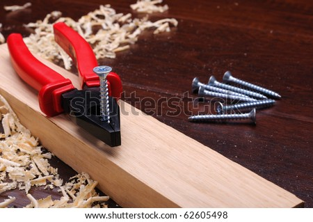 Shavings of wood, brick red and pliers on a dark background