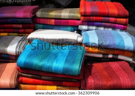 Shawls made from alpaca wood folded and piled for sale in the market