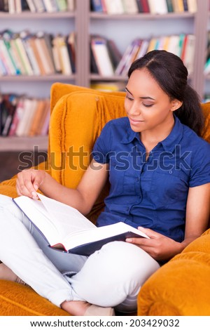 She found a peaceful place to read. Confident African female student reading a book while sitting at the chair in library - stock photo