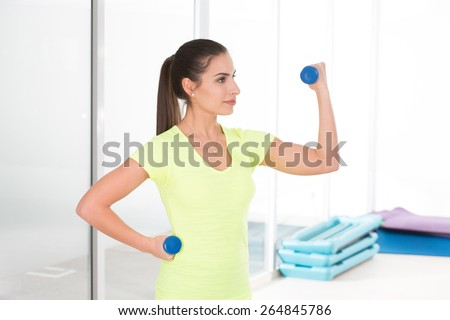 She has nice musculs, thanks dumbbels. Beautiful sporty woman in gym - stock photo