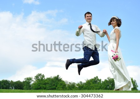 She holds his hand as he flits from happiness - a full-length portrait  of the bride and groom on a background of white and blue sky - stock photo