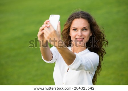She is awesome. Young beautiful woman take a picture of her self on phone outdoor. - stock photo