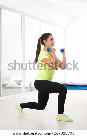 She is in yellow t-shirt make sit with dumbbell in gym. Beautiful sporty woman makes sport exercise - stock photo