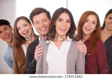 She is real leader. Attractive young woman smiling while group of cheerful young people standing behind her in two rows - stock photo