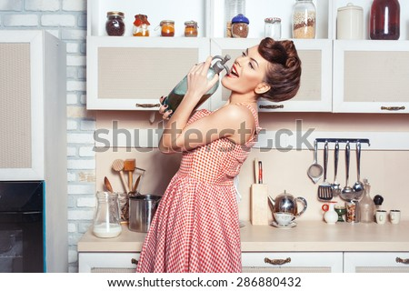 She is the mistress of the kitchen. She carried a bottle of soda. She sings in a bottle instead of a microphone. - stock photo