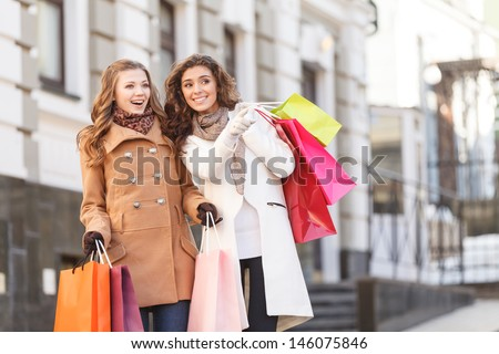 She knows where are the best prices. Two beautiful young women standing with shopping bags in their hands while one of them pointing away - stock photo