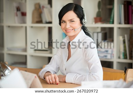 She like to speak with clients on phone. Portrait of white collar worker with headphones in office - stock photo