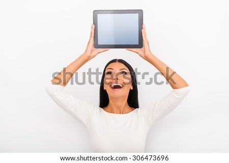 She likes smart gadgets. Cheerful young woman holding digital tablet above her head while standing against white background - stock photo