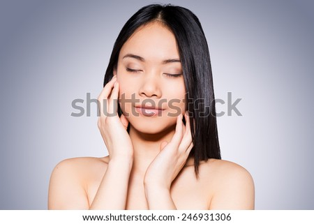 She loves her fresh skin. Portrait of beautiful young and shirtless Asian woman touching her face while standing against grey background   - stock photo