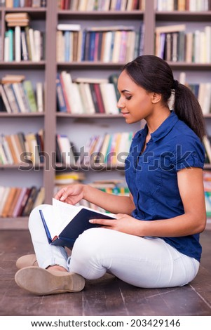 She loves reading. Side view of confident African female student reading a book while sitting on the floor in library - stock photo