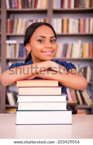 She loves studying. Confident young black woman leaning at the book stack and smiling while sitting at the library desk - stock photo