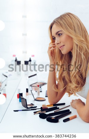 She loves what she sees. Side view of beautiful young woman looking at her reflection in mirror while sitting at the dressing table
