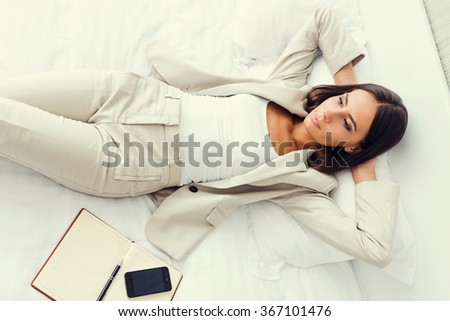 She need a break. Top view of beautiful young businesswoman in suit holding hands behind head and keeping  while lying in bed at the hotel room - stock photo