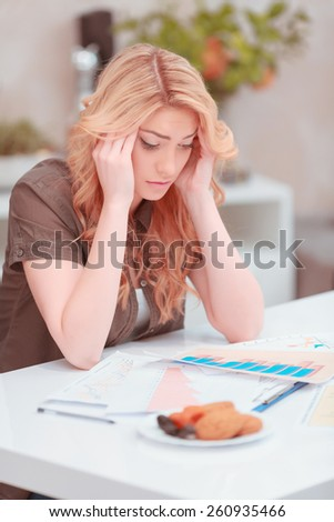 She needs help. Frustrated young woman in casual wear working with charts and analytics and touching her temples with fingers trying to understand