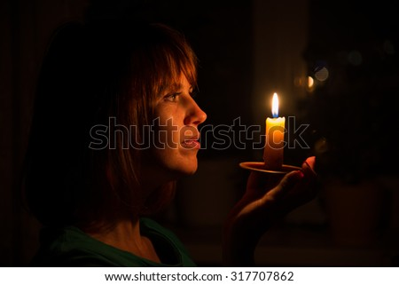 lighting for dark rooms. she shines a candle in dark room lighting for rooms