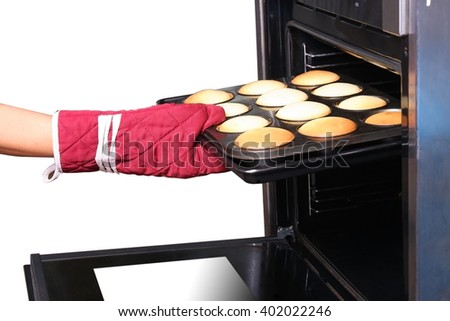 She taking cookies out of the oven - stock photo