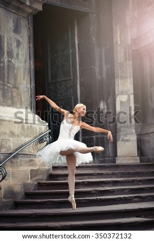 She went looking for inspiration. Full length portrait of a ballerina dancing gracefully near an old house - stock photo
