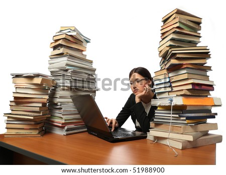 she works with the computer (a lot of books on the table) - stock photo