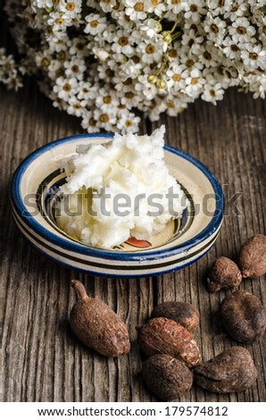 Shea butter and nuts on a wooden table with flowers in the background - stock photo