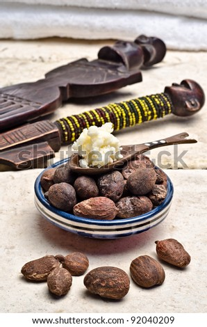 Shea nuts in a dish with a wooden spoon of shea butter - stock photo