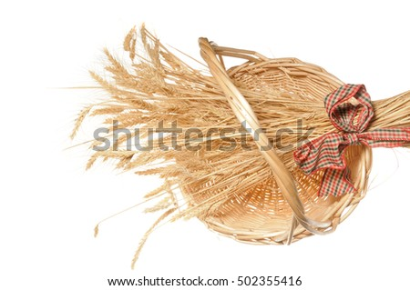 Sheaf of wheat in a wicker basket isolated on white