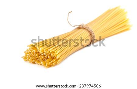 sheaf raw spaghetti on a white background isolated - stock photo