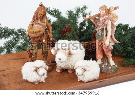 Sheep and shepherds bottom branches and pine cone on wood