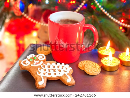 Sheep shape gingerbread cookie with cup of coffee on illuminated christmas tree background. Festive indoors still-life. - stock photo