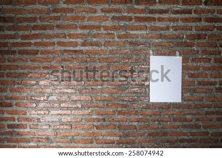 Sheet a paper, hanging on a brick wall - stock photo