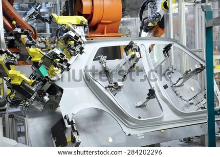 Sheet metal stamped part for the new car in the car factory. The robot holds part for new car. - stock photo