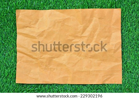Sheet of brown paper on green grass useful as a background - stock photo