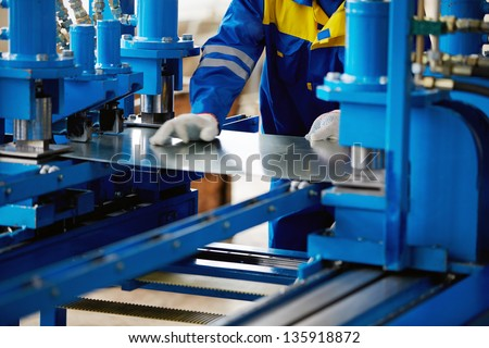 Sheet of metal and hands of worker who works on press - stock photo