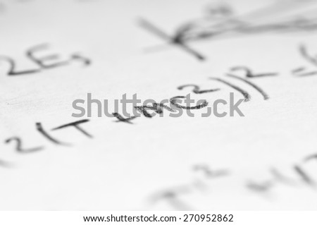 sheet of paper filled with calculations of nuclear and quantum physics as a background - stock photo