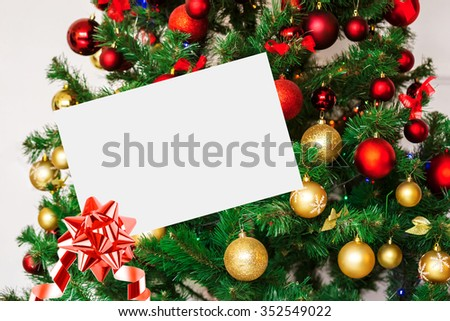 Sheet Of Paper With Bow And Ribbon On background Decorated Christmas tree. - stock photo