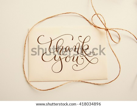 sheet of paper with bow  and text thank you. Greating card - stock photo