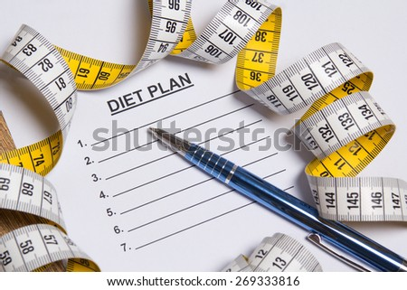 sheet of paper with diet plan, pen and yellow measure tape - stock photo