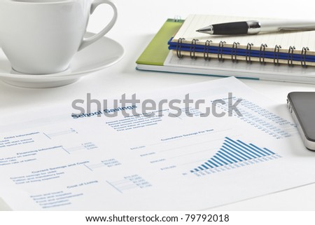 Sheet of paper with figures, tables and graph, small notebook and pen, cell phone and a cup of tea - stock photo