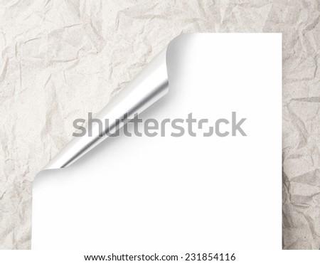 Sheet of paper with silver metal curl on a crumpled shabby beige paper texture - stock photo