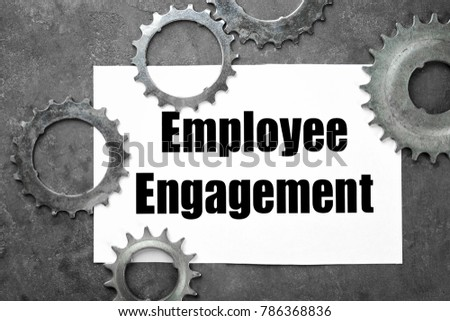 Sheet of paper with text EMPLOYEE ENGAGEMENT and tooth wheels on table