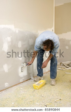 Sheetrock worker doing spot repairs on house walls, getting ready for new coat of paint, will put home on real state market to sell - stock photo