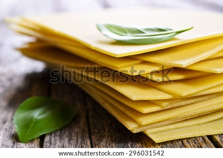 Sheets for lasagna with Basil leaves laid on a wooden surface - stock photo