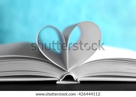 Sheets of book curved into heart shape on unfocused blue background - stock photo