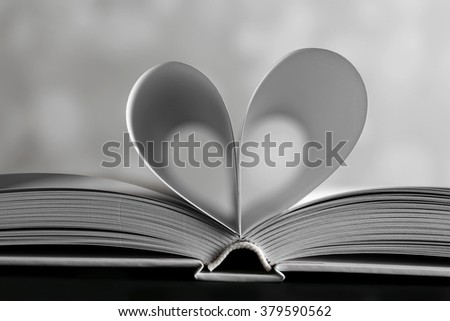 Sheets of book curved into heart shape on unfocused gray background - stock photo